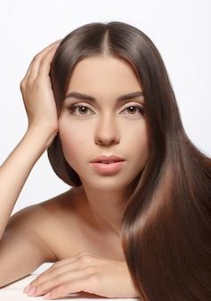 Mooie vrouw met lange bruine rechte haren - die op wit wordt geïsoleerd.