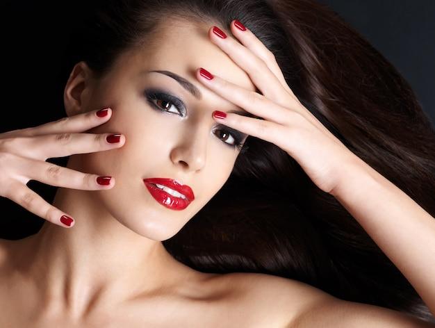 Mooie vrouw met lange bruine rechte haren en rode nagels die op de donkere muur liggen
