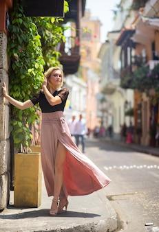 Mooie vrouw met lange jurk die alleen loopt in de kleurrijke straten van de koloniale ommuurde stad cartagena. colombia.