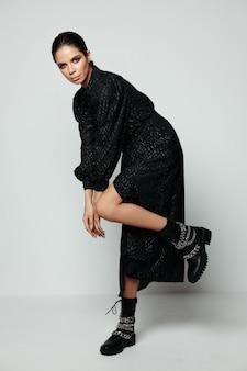 Mooie vrouw met lichte make-up in de zwarte laarzen van de kledingsmanier. hoge kwaliteit foto