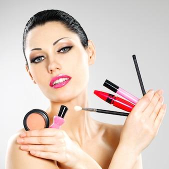 Mooie vrouw met make-up cosmetische hulpmiddelen in de buurt van haar gezicht.