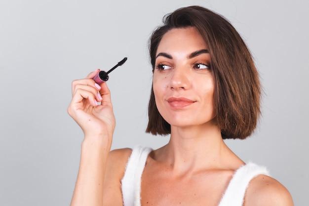 Mooie vrouw met make-up houdt zwarte mascaraborstel op grijze muur, schoonheidsconcept