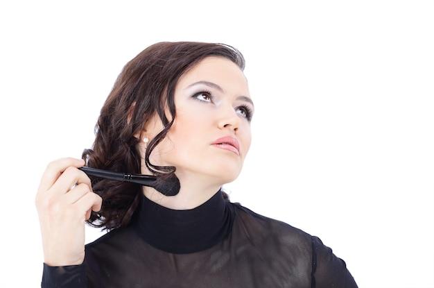 Mooie vrouw met make-upborstel dichtbij haar die gezicht - op wit wordt geïsoleerd