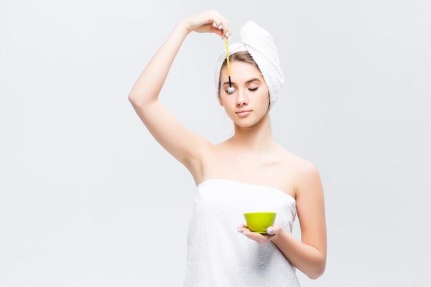 Mooie vrouw met make-upborstel die op witte muur wordt geïsoleerd