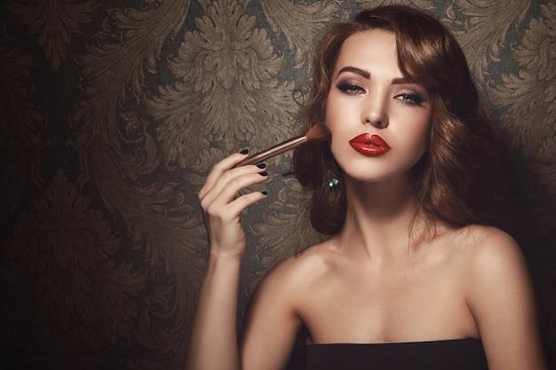 Mooie vrouw met make-upborstel