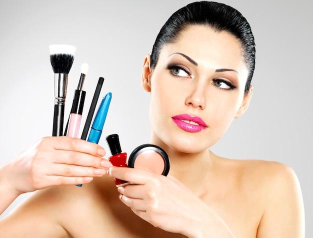 Mooie vrouw met make-upborstels dichtbij haar gezicht. mooi meisje vormt met cosmetische hulpmiddelen