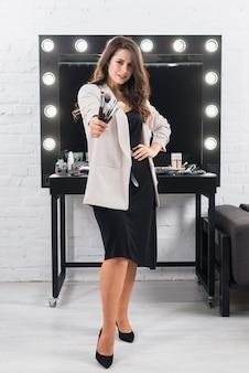 Mooie vrouw met make-upborstels die zich tegen de spiegel bevinden