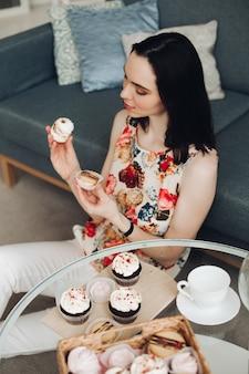 Mooie vrouw met marshmallow in handen. ze zit aan salontafel met zelfgemaakte cupcakes.
