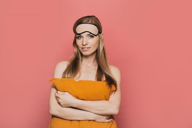 Mooie vrouw met masker voor slaap op haar hoofd, teder glimlachend, koesterend een oranje hoofdkussen, tevreden kijkend, over roze achtergrond.