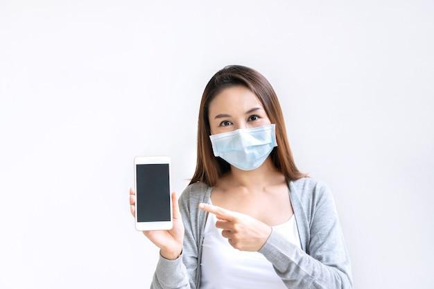 Mooie vrouw met medische gezichtsmasker smartphone voor kopie ruimte te houden