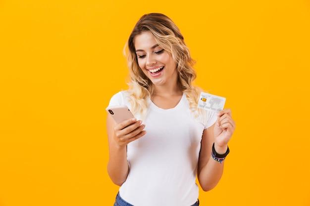 Mooie vrouw met mobiele telefoon en creditcard in handen, geïsoleerd over gele muur