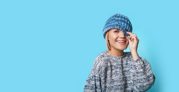 Mooie vrouw met modieuze hoed lacht op een blauwe muur met vrije ruimte