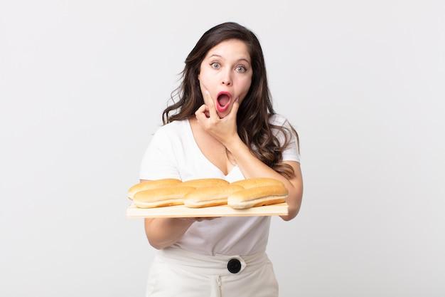 Mooie vrouw met mond en ogen wijd open en hand op kin en met een dienblad voor broodjes