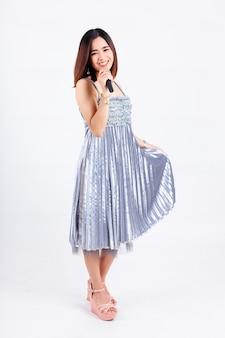Mooie vrouw met mooie jurk en draadloze microfoon