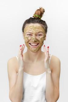 Mooie vrouw met natuurlijke schone de huidverjonging van het gezichtsmasker die op wit wordt geïsoleerd