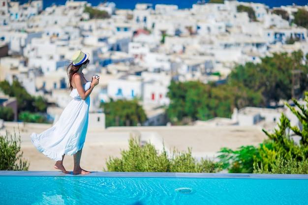Mooie vrouw met ochtendkoffie dichtbij pool met verbazend uitzicht op mykonos, griekenland