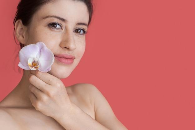 Mooie vrouw met ongeklede schouders houdt een bloem bij haar wang en lacht naar de camera op een rode muur met vrije ruimte