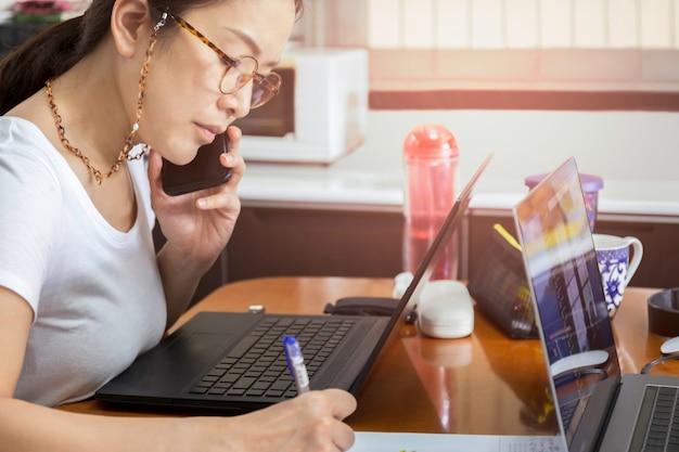 Mooie vrouw met oogglazen die op celtelefoon spreken met laptop thuis.