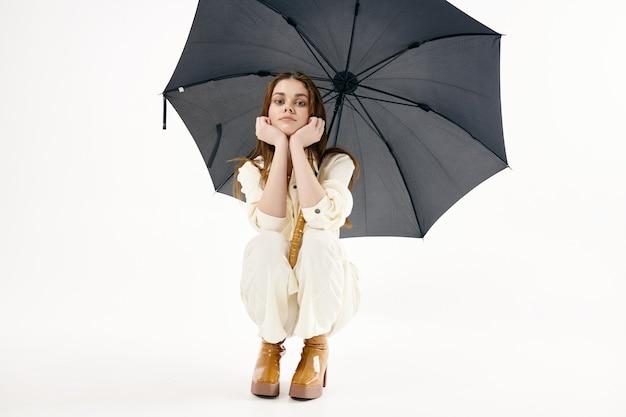 Mooie vrouw met open paraplu gehurkte mode