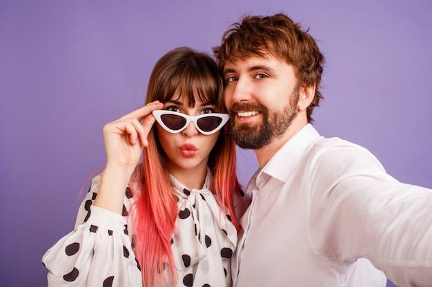 Mooie vrouw met openhartige glimlach en roze haar poseren met haar vriendje met baard