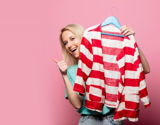 Mooie vrouw met overhemd op hanger op roze muur