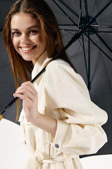 Mooie vrouw met paraplu in handen bescherming tegen regen licht pak