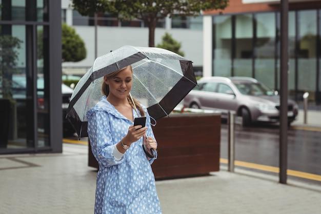 Mooie vrouw met paraplu tijdens het gebruik van de mobiele telefoon