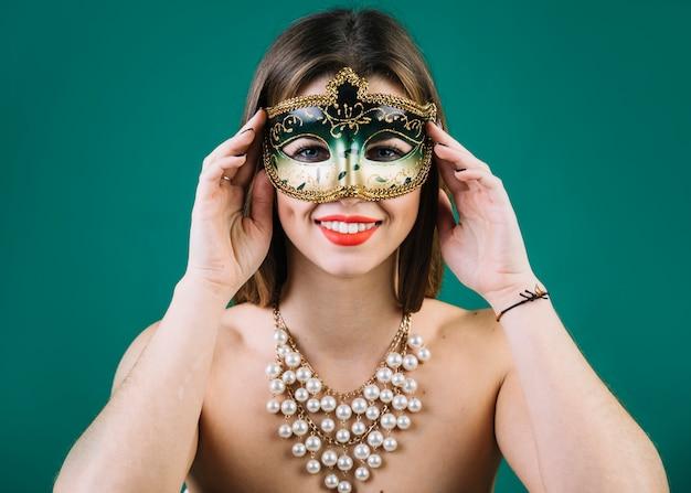 Mooie vrouw met parelshalsband en carnaval-masker op groene achtergrond