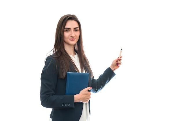 Mooie vrouw met pen en boek op wit wordt geïsoleerd