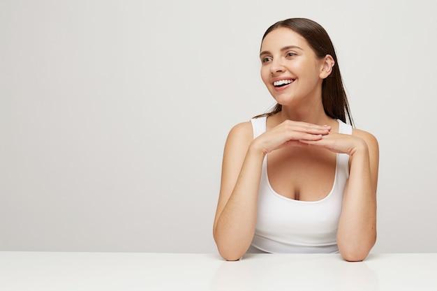 Mooie vrouw met perfect gezonde frisse huid zit aan tafel, kijkt opzij lachend