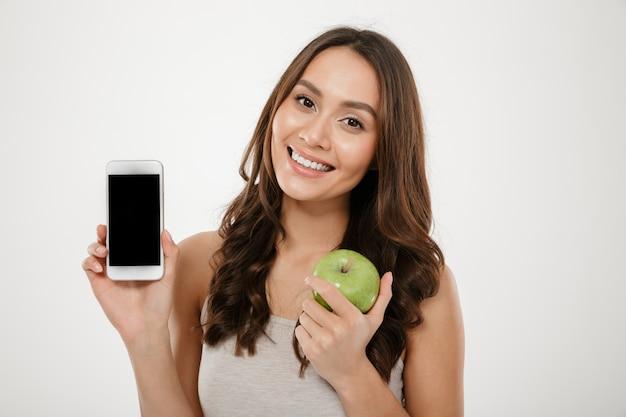 Mooie vrouw met perfecte glimlach die zilveren mobiele telefoon op camera aantonen en houden, groene appel die over witte muur wordt geïsoleerd