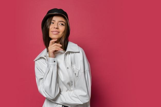 Mooie vrouw met perfecte glimlach gekleed in stijlvolle pet en witte jas die zich voordeed op roze achtergrond. isoleren.