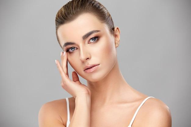 Mooie vrouw met perfecte lichte make-up wat betreft haar gezicht en op zoek, vrij jong meisje