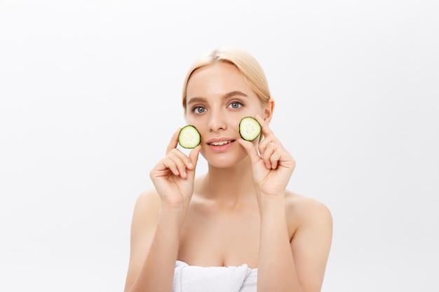 Mooie vrouw met plakjes komkommer in de voorkant van haar ogen