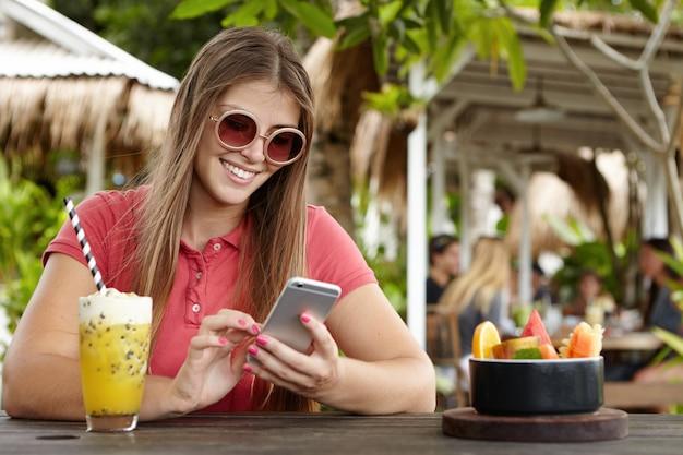 Mooie vrouw met poloshirt en ronde zonnebril surfen op internet op haar slimme telefoon, genieten van online communicatie tijdens de lunch op terrasje