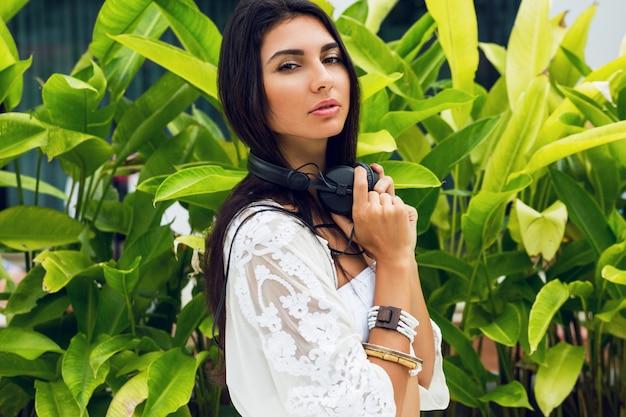 Mooie vrouw met poseren in moderne strandclub stijlvolle grote koptelefoon te houden