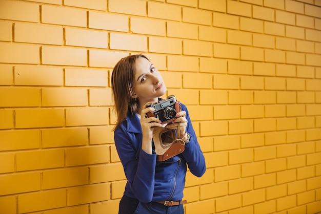 Mooie vrouw met retro filmfotocamera op gele bakstenen muur
