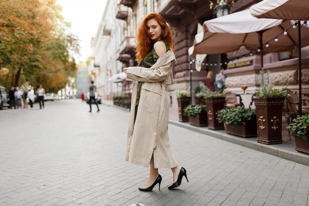 Mooie vrouw met rode haren en lichte make-up lopen op straat. beige jas en groene jurk dragen.