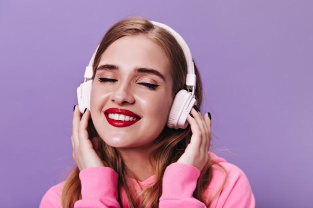 Mooie vrouw met rode lippen die lacht en geniet van muziek in een koptelefoon