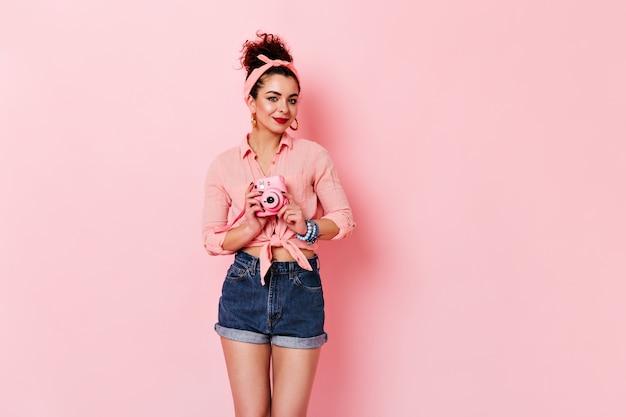 Mooie vrouw met rode lippen houdt roze camera. meisje met broodje en hoofdband gekleed in blouse en denim shorts poseren op geïsoleerde ruimte.