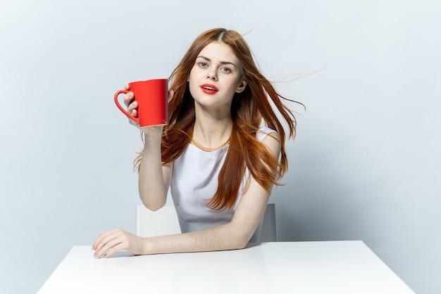 Mooie vrouw met rode lippen zittend aan tafel een kopje met een drankje ontspannen in een café.