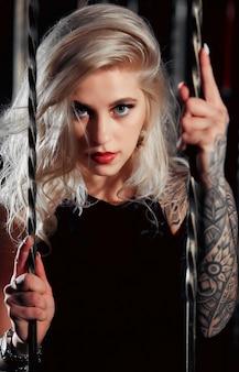 Mooie vrouw met rode lippenstift en tatoeages