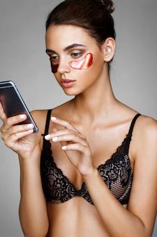 Mooie vrouw met rode ogen patches, kijkt op de telefoon