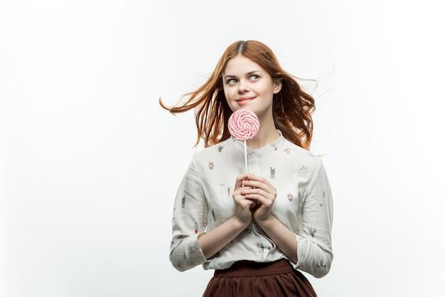Mooie vrouw met ronde lolly in de buurt van de snoepjes van het gezichtsplezier