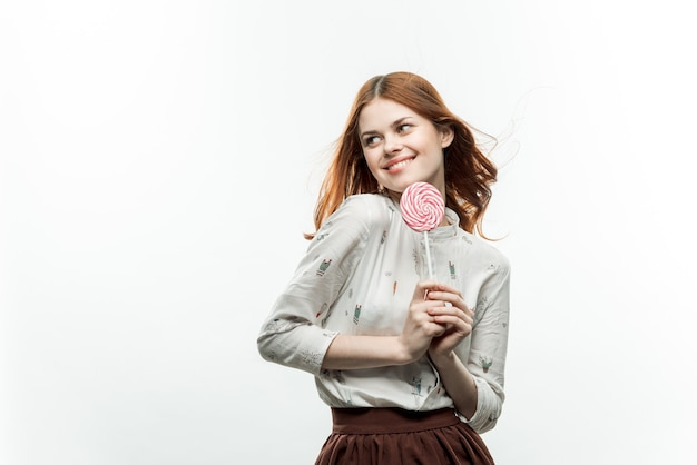 Mooie vrouw met ronde lolly in de buurt van snoepjes van gezichtsplezier