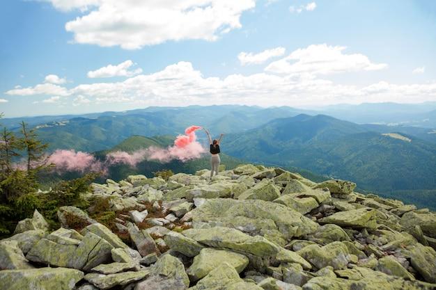 Mooie vrouw met rood gekleurde rook op de top van de berg en bewolkte hemelachtergrond