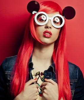 Mooie vrouw met rood haar die een grote zonnebril draagt