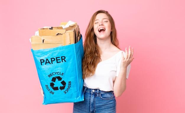 Mooie vrouw met rood haar die er wanhopig, gefrustreerd en gestrest uitziet en een zak van gerecycled papier vasthoudt