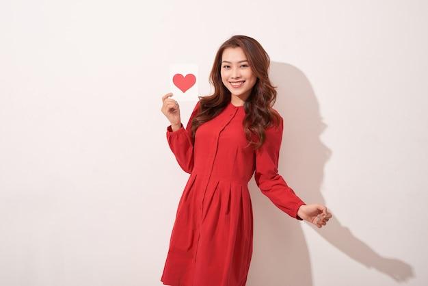 Mooie vrouw met rood hart geïsoleerd op grijze muur, viering van valentijnsdag, romantische gevoelens, harmonie en liefde concept