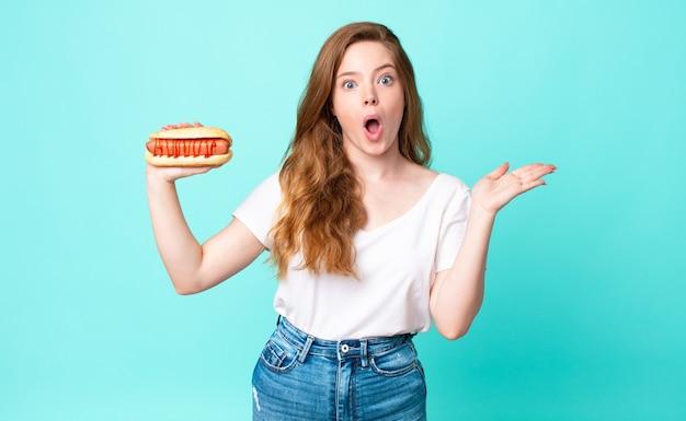 Mooie vrouw met rood hoofd die verrast en geschokt kijkt, met open mond terwijl ze een voorwerp vasthoudt en een hotdog vasthoudt